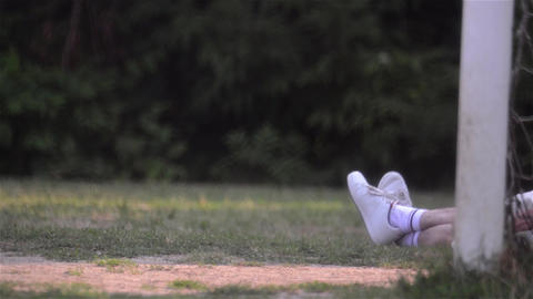 Legs Of An Athlete Who Is Resting Near The Gate Football While Another Man Walks stock footage