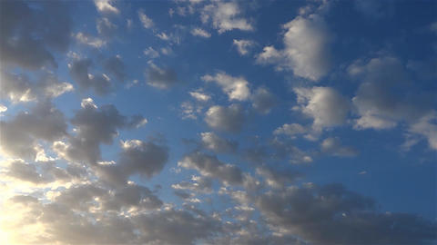 Fluffy clouds across the sky who is running and who are illuminated by sunset 23 Footage
