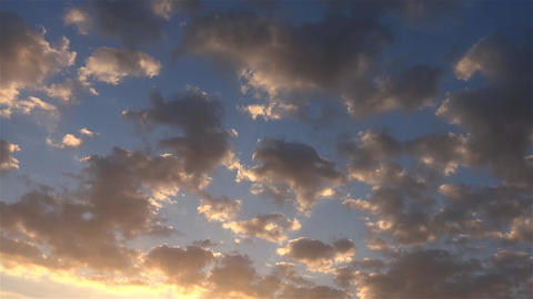 Fluffy clouds crossing the blue sky illuminated by the last rays of the sun 19 Footage