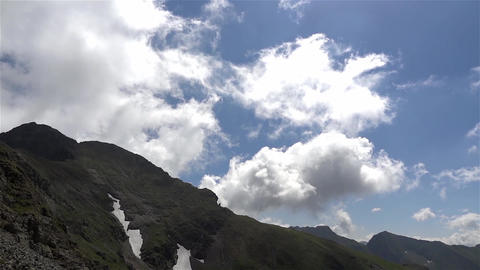 White clouds and thin passing in speed over snow covered mountain crests 31 Footage