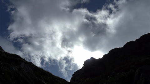 White clouds and thin passing in speed over the mountain crests 30 Footage