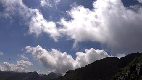 White clouds and thin passing in speed over the mountain crests 32 Footage
