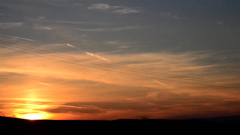 Sunset over a flat plain and an airplane flying in the sky 15 Footage