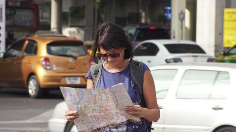 Attractive woman reading tourist map on city street Footage