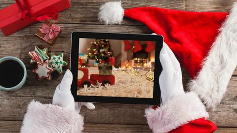 Santa using tablet with Christmas home Animation
