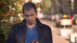 Caucasian man watching into smartphone changing emotions from indignation to Footage