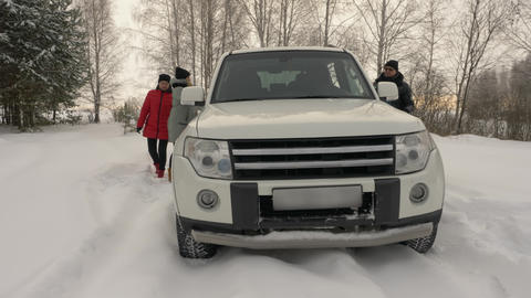 Family mother, father and daughter gets in car standing in snowy winter forest Footage