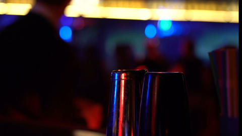 Bar shakers on table on dancing man background, night life enjoyment, alcohol Live Action