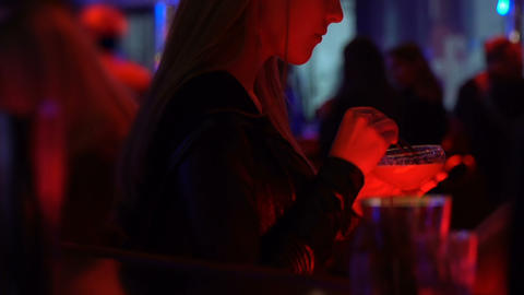 Attractive female relaxing in night club with cocktail, city entertainment Live Action