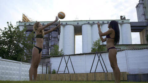 Two beautiful girls playing volleyball in sexy bikini outdoor. Rest of two sexy Live Action