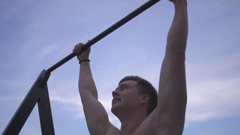 Young sporty naked guy pulls himself up on the horizontal bar outdoor on the Footage