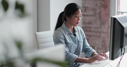 Young adult female working in an office on a desktop computer Live Action