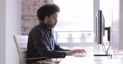 Male african american business executive working in an office on a desktop Live Action