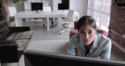 Young adult female standing and working on a desktop computer Live Action