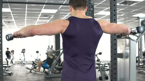 Sportive man performing lateral raise, training with dumbbells in gym, back view Live Action