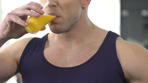 Sportsman drinking orange juice, refreshing beverage after intensive training Live Action