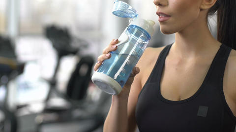 Sportive woman drinking fresh water after training gym, restoring aqua balance Live Action