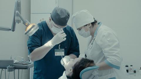 Dentist surgeon does the surgery 영상물
