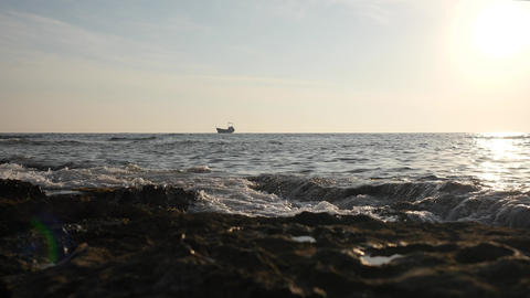 Small freight ship sail by the morning sea and waves cover the stone beach ビデオ