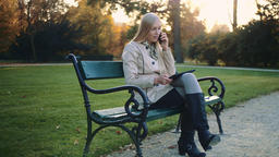 Young blonde girl with tablet computer and cellphone sitting on park bench Footage