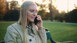 Smiling Blonde Woman with tablet computer and cellphone sitting on park bench Footage