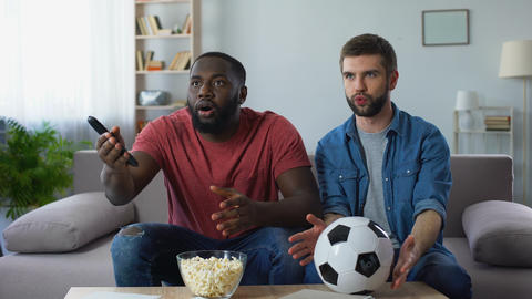 Multiethnic guys watching football match, frustrated by defeat of favourite team Footage
