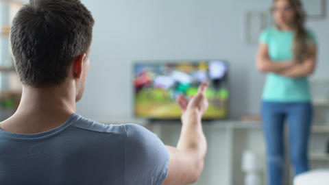 Girl nervously screaming at guy, forbidding him to watch tv sports competition Live Action