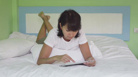 Attractive woman using tablet in bed Footage