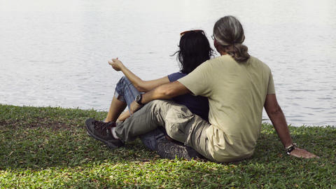 A Loving Couple Sit By Lake Looking At The Water stock footage