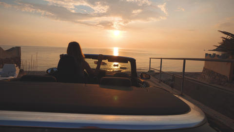 Girl dances on driver place in cabriolet car. Gentle colors of sunset over sea ビデオ