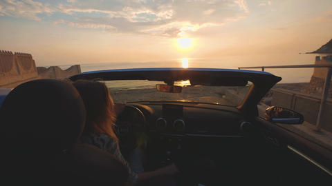 Woman sings and dances on driver place in convertible car. Sunset over sea Footage