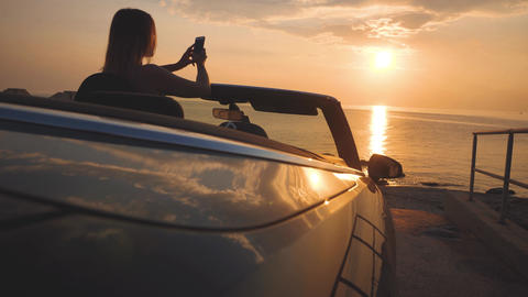 Female driver of luxury car takes s a photo of sunset seascape by cellphone Live Action