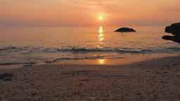Sunset over the sea. Sunlight blinks on water surface. Gentle surf rolls on Live Action