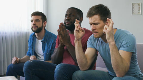 Men watching sport and praying for team winning, superstitious gestures, hope Live Action