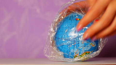 Globe wrapped in plastic wrap. Waste management concept Footage