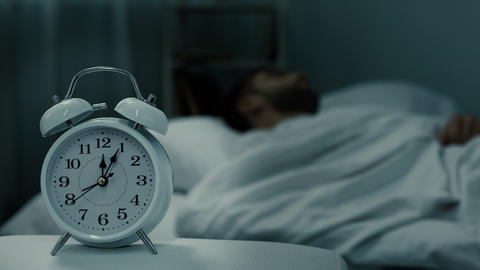 Bed clock showing midnight near sleeping man in bed, rest hours, healthy sleep Live Action