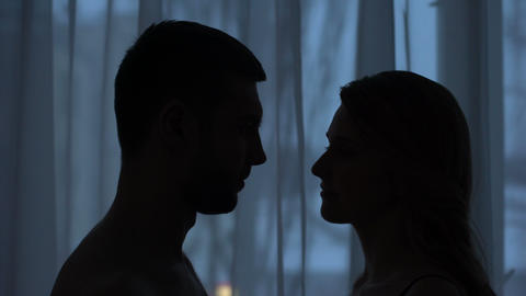 Man and woman silhouettes kissing in dark room, romantic night, love feeling Footage