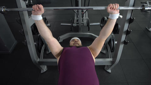 Plump male lifting up barbell hardly finishing set, desire to be strong and slim Live Action