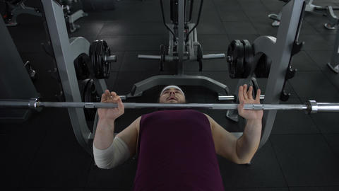 Man with elbow bandage trying lift up barbell, sport trauma, recovery therapy Footage