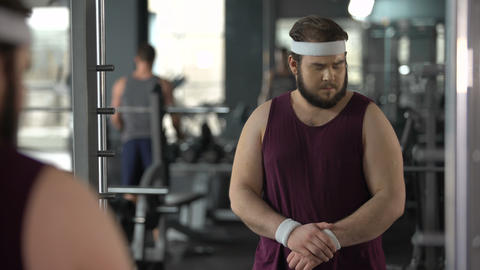 Unhappy overweight man looking at his mirror reflection in gym, diet and sport Live Action
