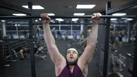 Chubby man pulling up on bar, desire to lose weight and be strong, motivation Live Action