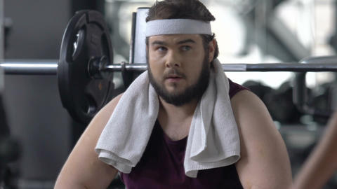 Funny obese man looks enviously at athlete people training in gym, insecurities Live Action