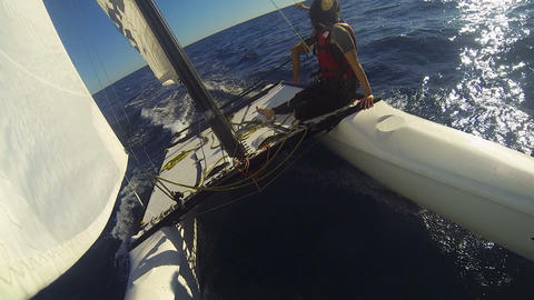 Windsurf catamaran going rapidly in ocean with two people on edge, extreme Footage