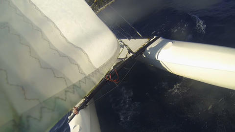 View of hulls and sail of windsurfing catamaran sailing on waves at high speed Live Action