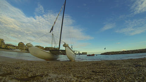 Pebbly coast with windsurfing catamaran, sunset sky and city at back, tourism Footage