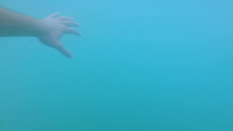 Guy swimming under water, looking around through blue water, point of view Footage