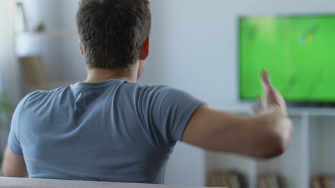 Emotional fan watching football game on TV at home, disappointed with result Footage