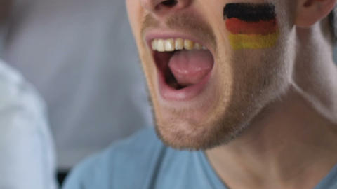 German football fan chanting and supporting team, watching game at stadium Footage
