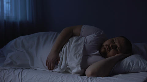 Obese man tossing in bed at night, sleeping disorder, insomnia disease, apnea Footage