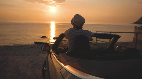 Man takes a picture of sunset and sea on cellphone from luxury cabriolet car Live Action